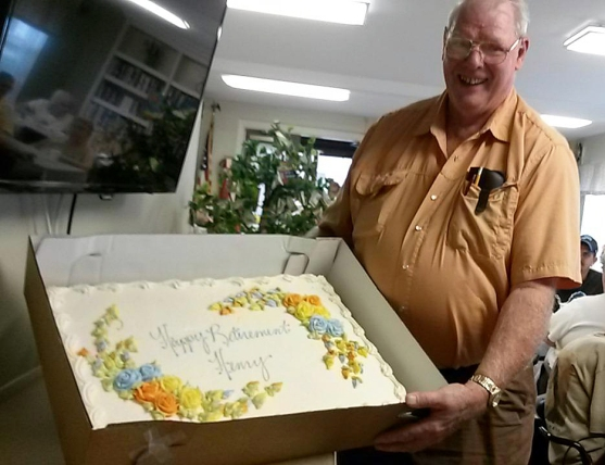 Henry Frazer holds up his cake at his retirement party. Henry's first day with National Church Residences was Sept. 24, 1990. He retired on Oct. 21.